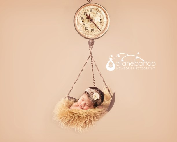 newborn girl on a vintage scale photo riverside