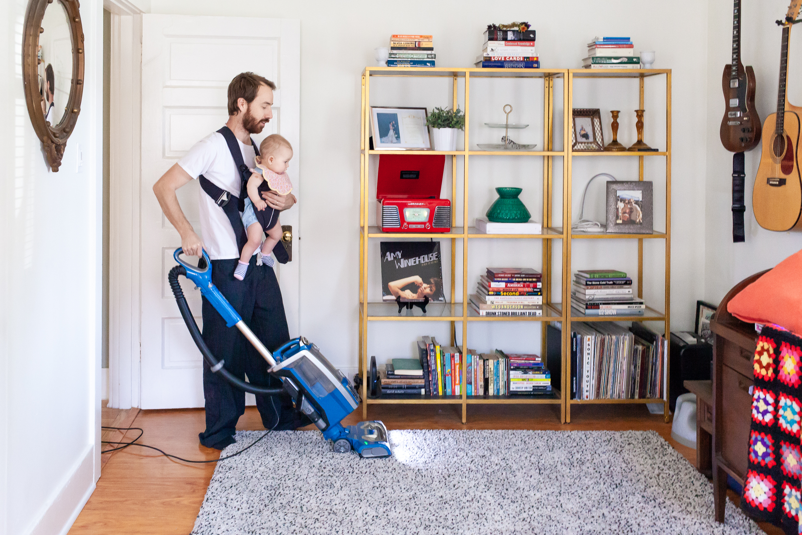 Documentary photograph showing a dad cleaning the house with a baby carrier and baby strapped to him