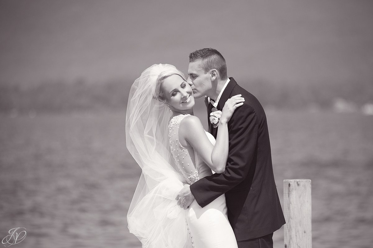 groom kissing bride cheek on lake black and white