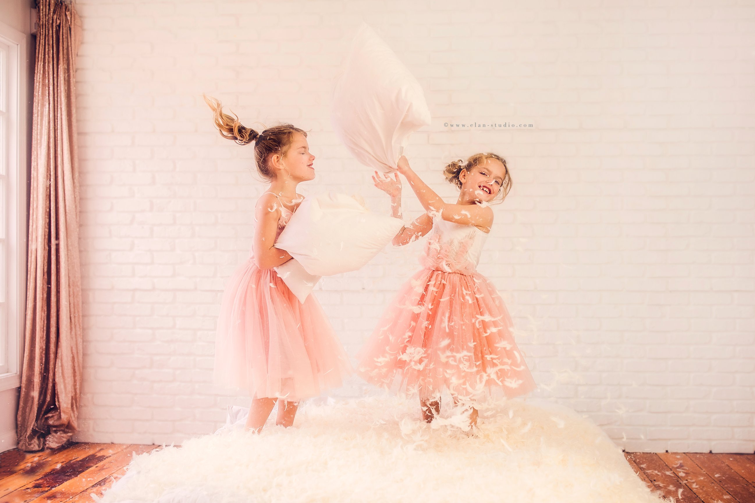 little girls having pillow fight in photography studio