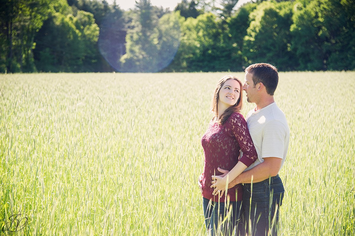 romantic photo of couple in a field with sun flair