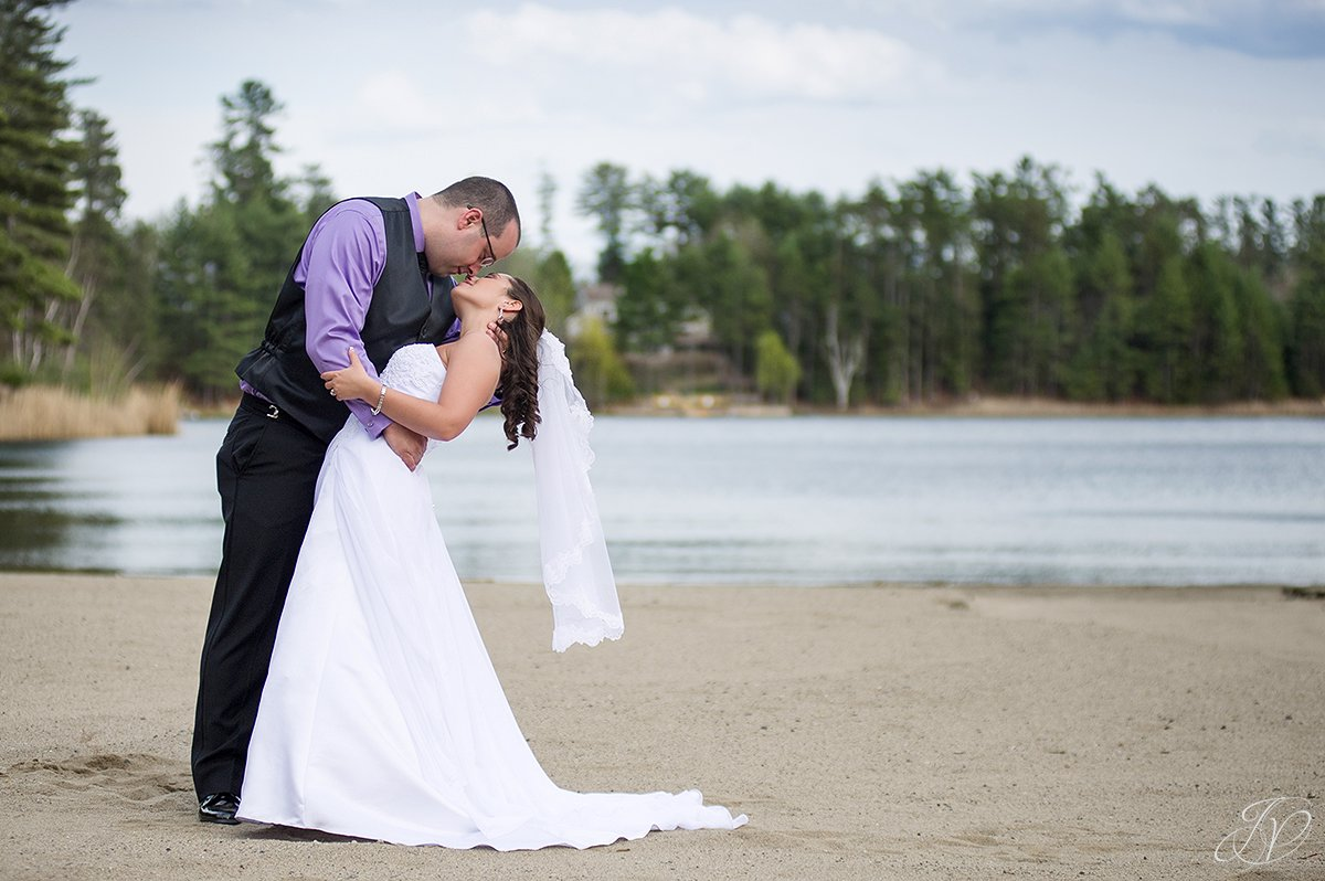 photo of groom dipping bride on the beach