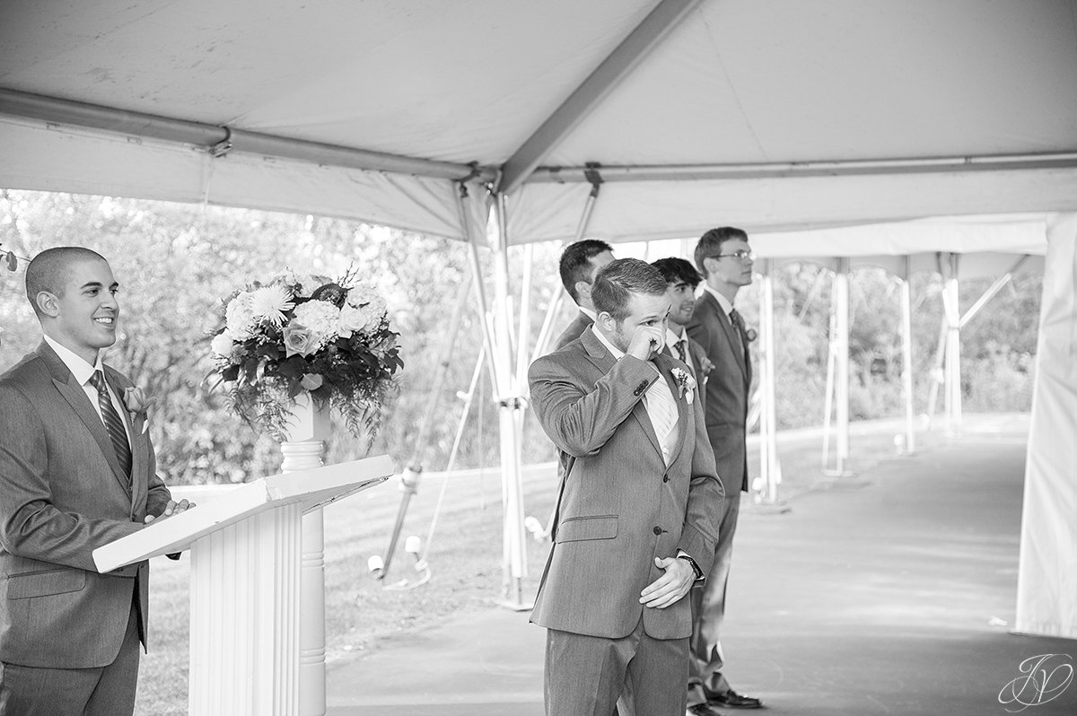 groom wiping away tears during ceremony