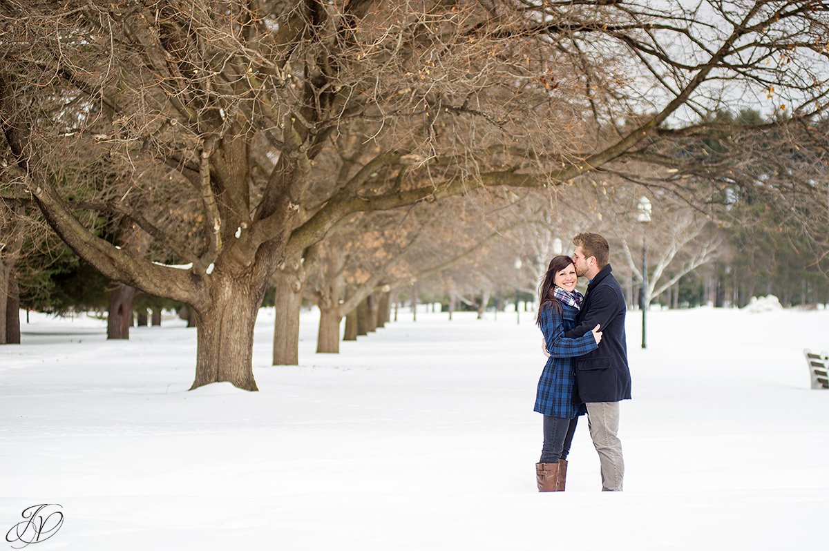 winter photo of engaged couple near row of trees