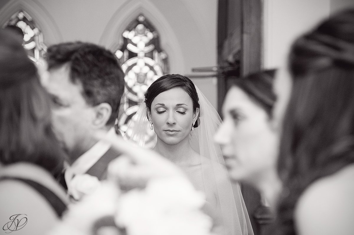 unique black and white photo of bride taking moment before ceremony