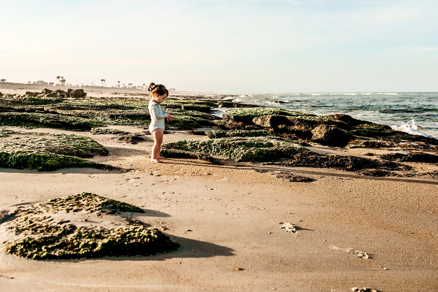 toddler girl among moss covered rocks at the beach, Florida, Ryaphotos