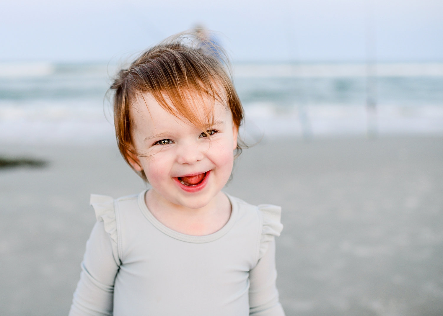 toddler girl smiling at the camera, Florida beach in the background, Ryaphotos